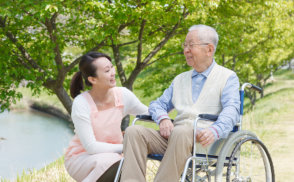 caregiver and senior man with wheelchair having a conversation