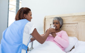 caregiver assisting sick senior woman to drink a water