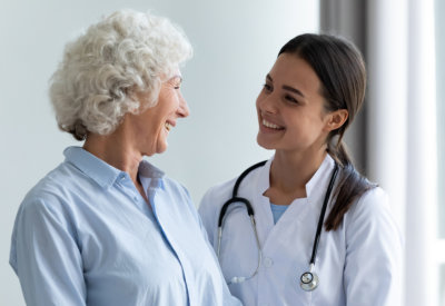 an elderly woman and a caregiver looking at each other and smiling