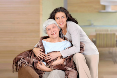 Elderly women and her daughter sitting in a chair with a blanket, hug, mother, grandmother