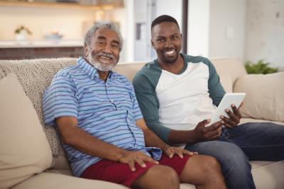 Portrait of smiling father and son sitting on sofa with digital tablet in living room