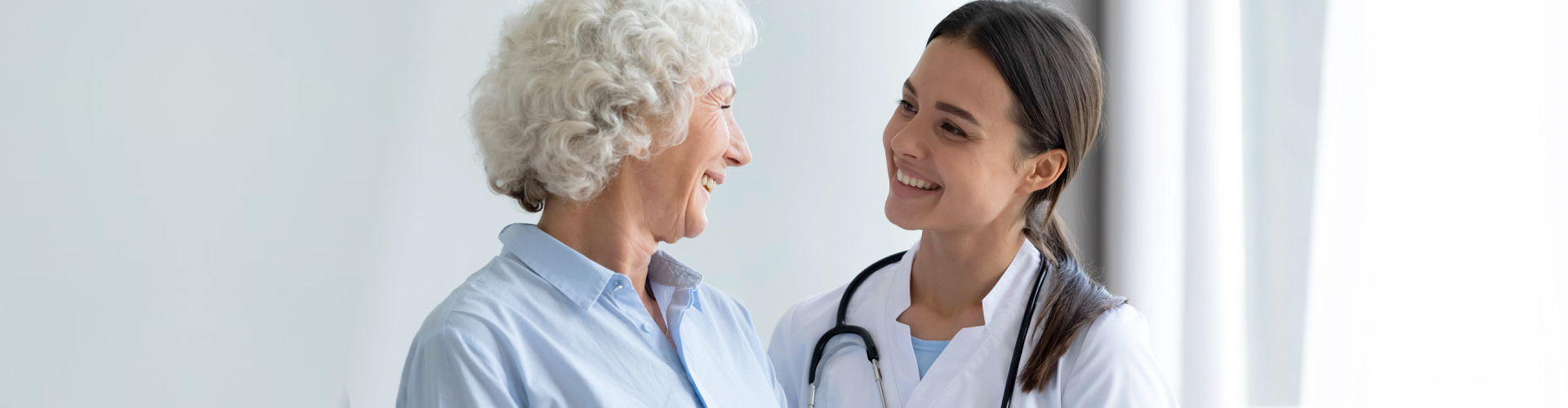 an elderly woman and a nurse smiling at each other