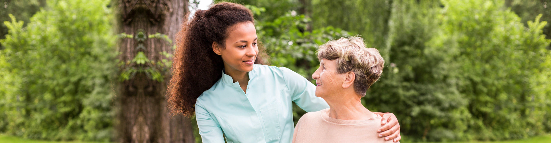 an elderly woman and her caregiver taking a walk outdoors